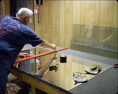 Service tech cutting a mirror